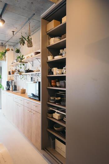 天井までの高さがある大きなキッチン収納。こちらのお宅では、スライドドアを取り付けたストレージが、食器や食材のストックを収納するパントリー代わりになっているのだとか。