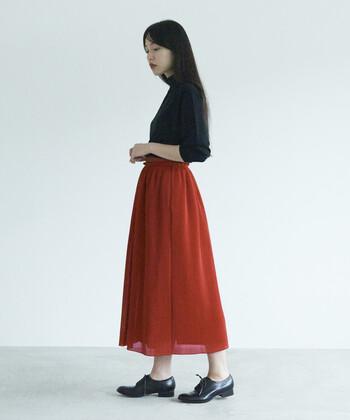 同じフレアなシルエットでも、シャンタン生地のスカートは独特のレトロな雰囲気が。赤の印象的なスカートにシンプルな黒のカットソーをインして、大人っぽく上品に。