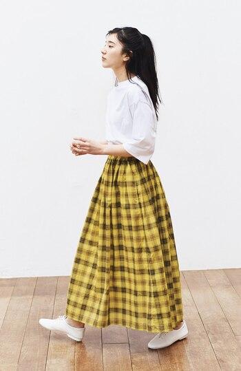チェック柄が目を引くスカートをメインに、マスタードイエローとホワイトの2色で統一。ゆったり白トップスのやわらかさが、ふんわりとしたロングスカートとマッチしてナチュラルで可愛らしい印象に。