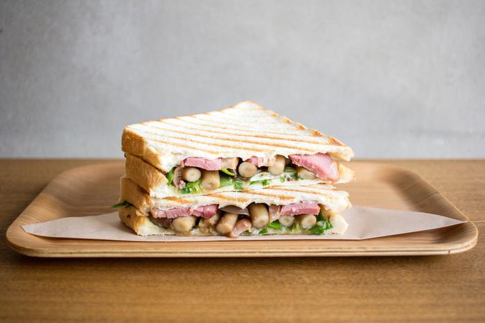 オリジナルメーニューの「鴨葱サンド」は、京野菜を代表する九条ネギをふんだんに使い、さらに鴨肉とシメジがたっぷりサンドされたボリューム満点なサンドイッチです。注文してから作ってくれるので、いつもアツアツの状態で食べられるのが嬉しいポイント。シメジとネギのシャキッとした食感も楽しい味わいになっています。