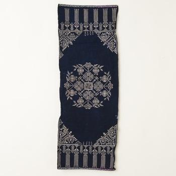 中国の苗族によって作られた、藍染めに金の刺繍が施されたのれん。複雑で繊細な模様は、ずっと眺めていたくなる美しさです。