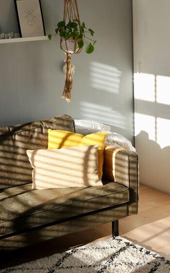 アースカラーのソファーに単色イエローと柄入りイエローのクッションをセットで配置。お部屋全体が暖かみにあふれ、ぐっと明るい印象になります。