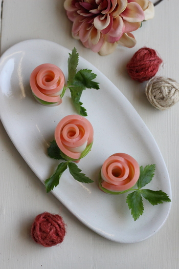 こちらは薄く切ったかまぼこと、三つ葉で作るおしゃれなバラの飾りです。ピンクとグリーンの彩も綺麗ですね。見た目はおしゃれなのに、作り方はとっても簡単。お弁当に一品添えるだけで、豪華な雰囲気になりますよ。