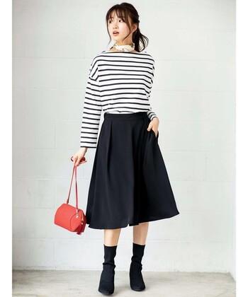 ボートネックの白黒ボーダートップスに、ネイビーのひざ下丈スカートを合わせたコーディネートです。足元は黒のブーツをチョイスして、ダークトーンでまとめています。手元の赤バッグと首元のスカーフが、程よいアクセントに◎