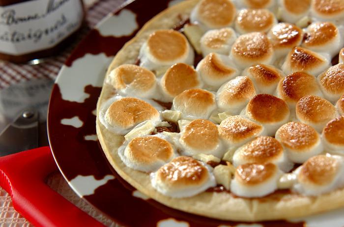 市販のピザ生地にチョコレートとマシュマロをのせて焼いたら、スイーツピザとしても楽しめます。 こちらは、溶かしたミルクチョコレートをソースがわりにしいて、その上に砕いたホワイトチョコとマシュマロのせて焼いています。マシュマロは焦げやすいのでオーブンから目を離さないようにしましょう。
