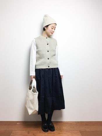 前開きのニットベストを、シンプルな白シャツとネイビーのフレアスカートに合わせたスタイリングです。フロントに並んだボタンが、ナチュラルコーデの程よいアクセントに活躍してくれます。ベストと色を揃えたニット帽で、季節感もしっかりアピール♪
