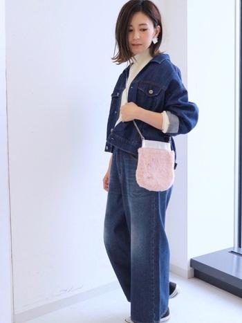 上下ともデニム素材のカジュアルコーデ。ピンクのファー素材のバッグで女性らしさを出して。