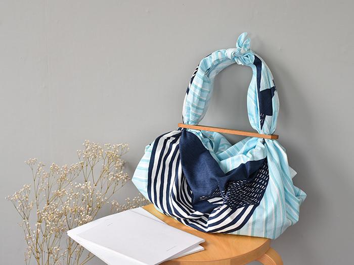 「ふろしきパッチン」の場合には木のパーツの4隅にある穴に布を通し、布の端を結んで持ち手を作ります。和・洋どんな柄の布ともコーディネートしやすい、シンプルなデザインとナチュラルな素材感も魅力的です。こちらも以下のリンク先のページで、バッグの作り方が動画で紹介されています。ぜひ参考にしてみてくださいね。
