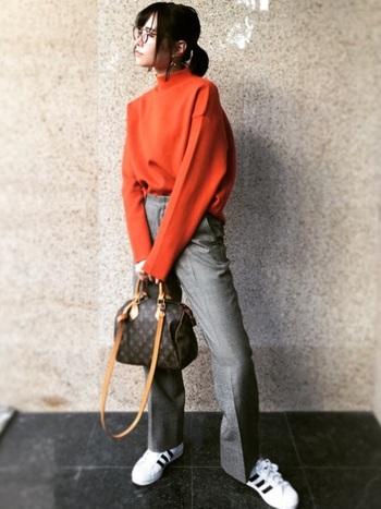 鮮やかなオレンジニット×グレーのトラッドパンツの組み合わせ。ポップなカラーをメンズライクコーデに落とし込んで差し色に。レトロなモノグラムのバッグも新鮮なイメージです。