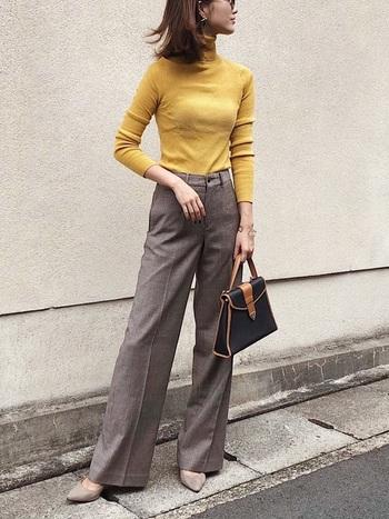 くすみイエローのタートルニットに、グレージュのスラックスパンツを合わせたきれいめスタイル。タイトなシルエットが女性らしさを、ヒールパンプスときかっちりバッグで大人っぽい印象です。
