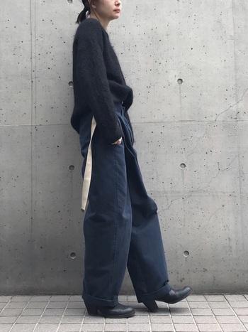 ゆったりとした黒ニットをネイビーのワークパンツにイン。ビッグシルエットも着こなしの工夫たダークトーンでまとめることで、すっきり引き締まった印象に。
