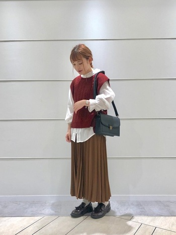 ボルドー系の赤ニットベストに、白シャツとベージュのプリーツスカートを合わせたコーディネートです。黒のショルダーバッグとローファーシューズで、レトロなカラーリングのアイテムに引き締め感をプラスしています。