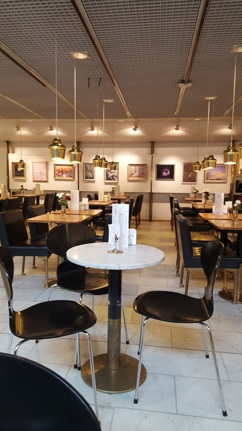 """1969年、フィンランド・ヘルシンキ市内にあるアカデミア書店内に併設されたカフェとしてオープンしました。店内には、アアルトの代表作である""""ゴールデンベル""""のペンダントランプや、デンマーク出身のデザイナーArne Jacobsen(アルネ・ヤコブセン)氏のチェアーなど、北欧ファンにはたまらない、インテリアに仕上がっています。"""