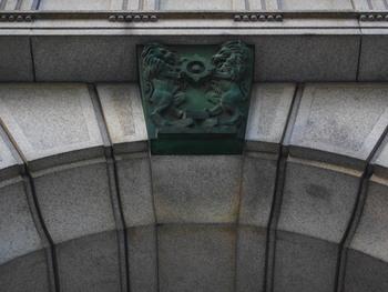 正面玄関入り口にある青銅製の紋章は、二頭のライオンが千両箱を踏まえて立ち、「めだま」を抱えているという大変ユニークなものです。「めだま」は日本銀行のシンボルマークで、「日」という古代書体をアレンジしたものだそう。  最寄りのバス停は「メトロリンク日本橋」の「三井記念美術館」になります。