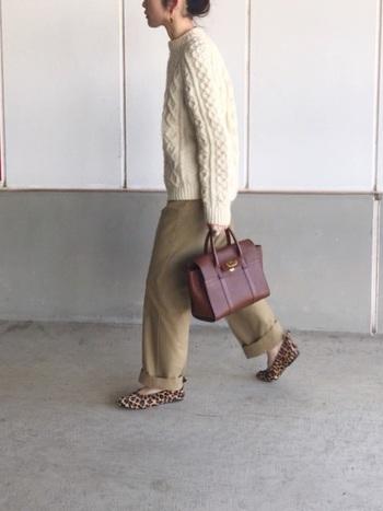 ざっくりとしたオフホワイトのアランニットにチノパンを合わせたスタイル。模様編みが温もりの表情を添えています。レザーバッグとレオパー柄のシューズも秋らしい雰囲気。