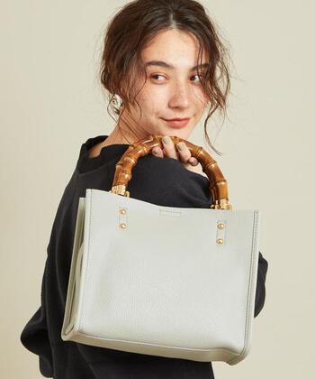 フェイクレザー素材の、バンブーハンドルバッグ。手持ちスタイルだけでなく、ストラップを付けてショルダーとしても使える2way仕様です。ブラック・グレー・オフホワイトの3色展開で、女性らしいニュアンスカラーも選べます。