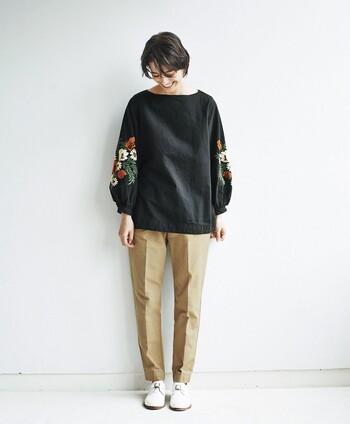 ベージュのセンタープレスパンツを、黒のゆったりトップスでラフに着こなしています。袖に花の刺しゅうをあしらったトップスをチョイスして、シックな中にも女性らしさを演出してくれる着こなしです。