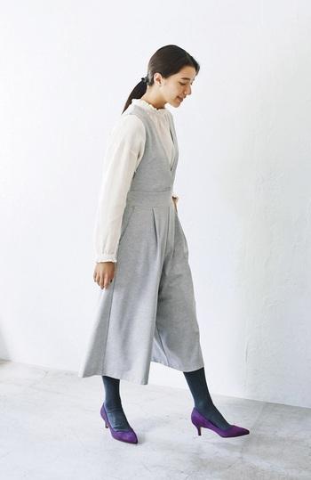 フェミニンな雰囲気を与える、カットソー素材のサロペットパンツを、白のブラウスで爽やかに着こなしています。足元はネイビーのタイツとパープルのパンプスで、季節感をアピール。落ち着いた大人の女性にぴったりな、レディライクコーデに仕上げています。