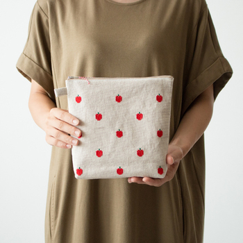リネンアイテムのファクトリーブランドALDIN(アルディン)の、一面にりんごが刺繍されたキュートなポーチ。
