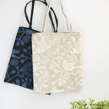 鳥と草花をモチーフにした繊細な刺繍が施された手提げバッグ。ナチュラルな印象のベージュと、大人っぽくシックな印象のネイビーの2種類。