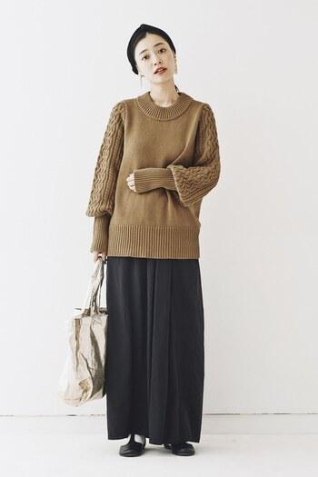 袖のケーブル模様が特徴的なニット。ブラックのボトムスで合わせるとシックな秋の装いに仕上がります。飽きずに楽しめるコーデです。