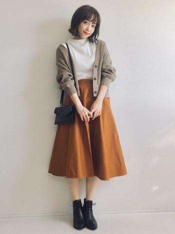 明るめのブラウンのスカートが印象的なコーデ。革のショートブーツでキチンと感を演出。