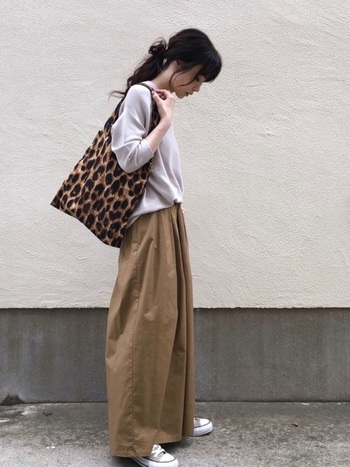 一見スカートにも見えるブラウンのワイドパンツに、ベージュのニット&スニーカーを合わせて。レオパード柄のバッグをセレクトして今年っぽく。
