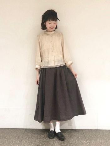 ダークブラウンのスカート×繊細なレースのブラウスの、フェミニンコーデ。ナチュラル素材のものを選べば、ダークな色でも重たい印象になりませんね。