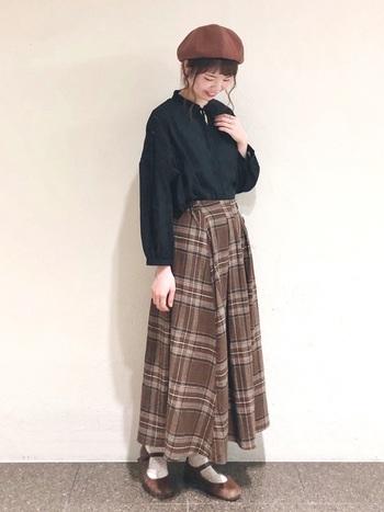 チェックのロングスカートにブラウスという女性らしいコーデに、ブラウンのベレー帽とストラップシューズを合わせて可愛らしさをプラス。ヘアスタイルはキチンとまとめるより、後れ毛を出して抜け感を演出。