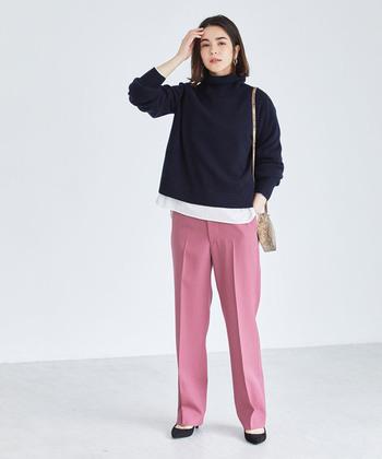 ネイビーのタートルニット×ピンク色のきれいめパンツコーデ。メンズライクな中にほんのり女性らしさを香らせて。白シャツの裾を覗かせて、明るさを加えるのもポイントです。