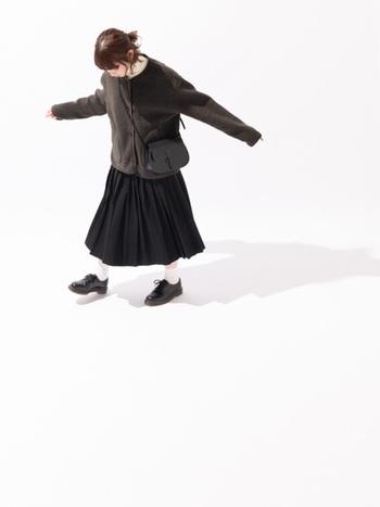 ボアのジャケットにスカートを合わせて、ほっこりと可愛らしい印象のコーディネート。全体的に落ち着いたトーンですが重たくならないのは、首元から明るい色のタートルネックのニットを見せて、足元にも白いソックスを合わせてヌケ感を出しているからかもしれません。コーディネートの色味がダークトーンになってしまいがちな秋冬に参考になる、素敵なスタイリングです。