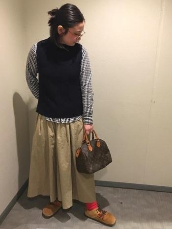 いつものコーディネートに、ニットベストを合わせるのも素敵です。チェックシャツとベージュのスカートのカジュアルなスタイリングにニットベストを合わせると、ちょっぴりハンサムな印象に。冷え対策にも良さそうですね。