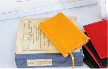 こちらは、上質な革素材で明るいカラーリングが魅力的な文庫本サイズのブックカバーです。革製のお財布やキーケースと一緒にカバンに入れておけばおしゃれ度アップ。カバーに付属したしおりの紐も革素材。使いやすさを考え、紙と並行な位置になるよう取り付けられているのだそう♪