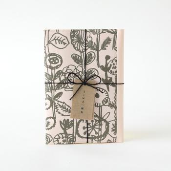 """こちらの文庫本サイズのブックカバーは「ソフトナオロン」という破れにくい和紙でできています。和紙の肌触りと革のような味わい深さが一緒になったアイテム。使うほどに手になじみ、段々と増える""""しわ""""によって、より素敵な装いに♪ミナペルホネン好きの方へのプレゼントにもおすすめ。"""