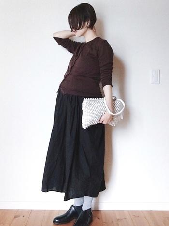 ブラウンのカーディガンと黒のスカートを合わせて、シンプルながらも小物を効かせてモード感漂うコーディネートに。カーディガンなら下のボタンを開けておなかまわりの調節がしやすく、妊婦さんでも無理なく着られそうです。