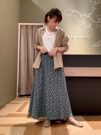 水色が綺麗な花柄スカートは、ベージュのシャツと白Tでシンプル&ラフに仕上げて。足元はスニーカーではなくフラットシューズを合わせることで、レディらしさも取り入れることができます。