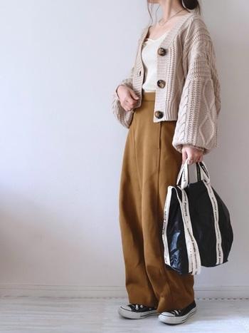 ベージュのざっくり編みカーディガンと合わせて秋を感じるスタイルを先取り。バッグとスニーカーはブラックでまとめてコーディネートを引き締めて。