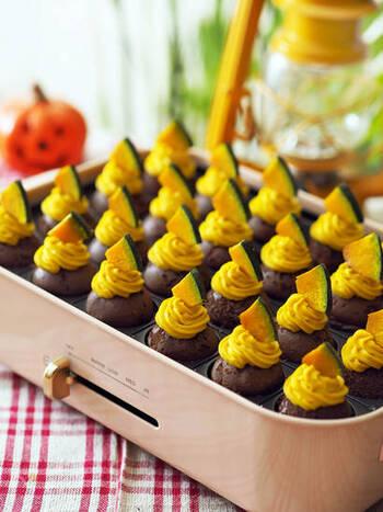 たこ焼きプレートいっぱいに並ぶ、可愛らしいパンプキンプチモンブラン。ホットケーキミックスとココアで作る生地を、たこ焼きプレートで丸く焼き、カボチャクリームを絞り、飾りのカボチャをのせるだけ。焼く行程からテーブルで皆で作っても楽しそう。