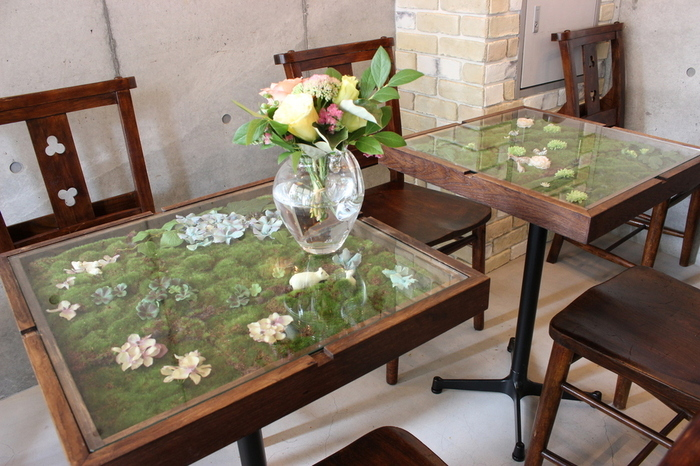 このお店で注目したいのは、ガラス天板のテーブルの中に作られたジオラマです。思わず写真を撮りたくなるジオラマには、旬のお花や小さな動物もひょっこり隠れていたり。フラワーコーディネーター、インテリアコーディネーターとして活動する店長・川本幸代さんが、季節ごとに自らデザインを手がけています。