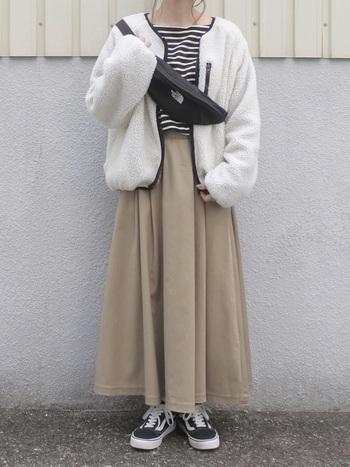 ベージュのフレアスカートに白のボアジャケットを。淡い色味で優しげな雰囲気に仕上がります。