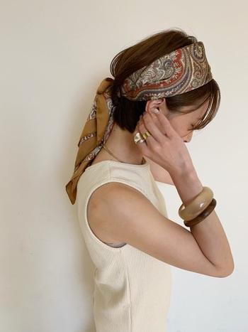 スカーフの結び目を後ろに持ってきたアレンジスタイル。結び目から下を長めに垂らすことで大人っぽい雰囲気になります。コーデはシンプルにまとめると、スカーフが映えて◎