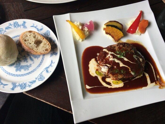 レストランの人気メニューはハンバーグ。どっしりしたハンバーグはふわふわの食感で、切ると肉汁が溢れ出てきます!デミグラスソースも濃厚で美味しいですよ。付け合わせのパンも、もちろん本格的なお味です。