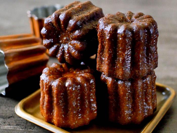 """""""溝のついた""""という意味を持つ「カヌレ」は、フランスにあるボルドー女子修道院で古くから作られていたお菓子で、蜜蝋を小さな型の内側に塗って作るのが特徴です。こちらのレシピでは蜜蝋は使われていませんが、バニラビーンズを使うなど本格派。ぜひ挑戦してみませんか?"""