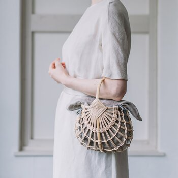 籐と竹を組み合わせ、繊細に編み上げたBasket。そのモダンで洗練された佇まいは、まるでアートピースのような美しさです。日常使いはもちろんのこと、ホテルでの会食などフォーマルなシーンにもおすすめです。大きさはSとLの2サイズを展開しています。(写真はSサイズ、インナーバッグは麻素材)
