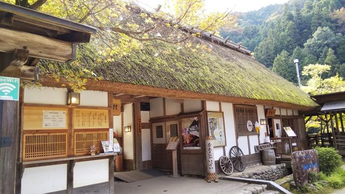 三州足助屋敷(さんしゅうあすけやしき)は、1980年から昔の暮らしを紹介するための博物館兼体験型複合施設としてオープンした、足助の有名観光スポットです。茅葺きの家は足助の大自然と見事に融合しています。