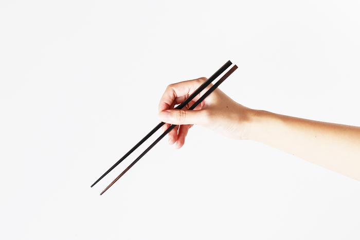 箸頭(はしがしら。箸の頭部)の直径は、お箸の中では一番細い5mm。素材は北海道産カバノキの積層材。1.5mmの板に熱硬化樹脂を含浸させ、重ねて熱圧プレスし、 防水性と耐久性を高めています。表面は植物性の蝋による仕上げ。華奢なフォルムは、持つひとの手指まで美しく見せてくれそう。