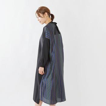 ウールトロピカル素材とストライプ柄を前後で切り替えたワンピース。フロントはコンパクトなクルーネックで上品に、バックは大きめのリボンとスリットで女性らしい雰囲気になっています。裾の切替しデザインもおしゃれですね。