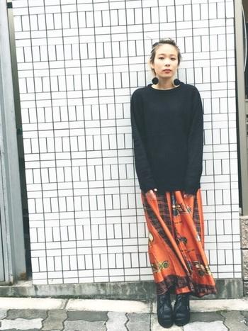 シンプルな黒のニットはメンズ物。インパクトあるオレンジ色の柄物スカートで印象的に着こなしていますね。