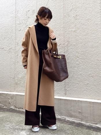 コートの前を開けておくことで、ニット&パンツの黒の縦長ラインを強調。