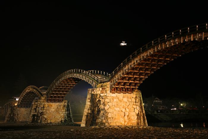 渡るだけでなく、橋全体を眺めてみましょう。周辺の自然との調和をじっくり堪能できます。昼は自然や岩国城との美しい錦帯橋を、夜はライトアップされた幻想的な姿が魅力です。